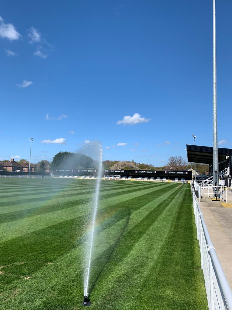 A sprinkler covers a football pitch in water