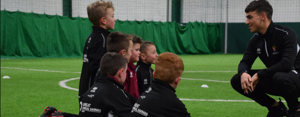 Coach issues instructions to kids on a football pitch